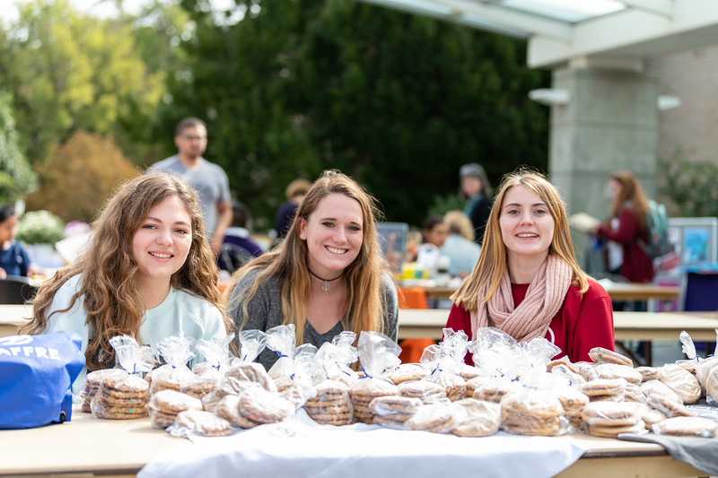Fernanda Canteu, Shelby Venjohn, and Janae Brown sell cookies for the Bakery Science Club at the Kansas State Farmers' Market in Bosco Student Plaza on September 26, 2018. (Alex Todd | Collegian Media Group)