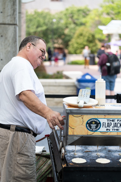 Pat from Chris Cakes has a flippin' good time serving up pancakes to students at the Kansas State Farmers' Market in Bosco Student Plaza on September 26, 2018. (Alex Todd | Collegian Media Group)