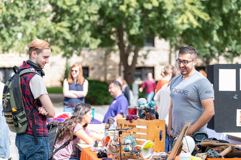 Victor Andrews, a graduate student in Public Health, talks with a student at this booth during the Kansas State Farmers' Market in Bosco Student Plaza on September 26, 2018. (Alex Todd | Collegian Media Group)
