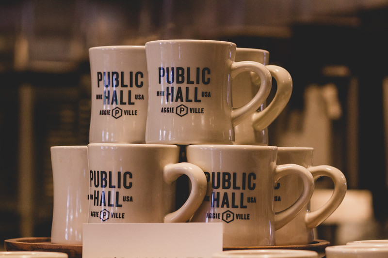 Coffee mugs available to purchase sit on the counter at Public Hall. After opening in September, Public Hall has quickly become a popular spot for students. (Andrea Klepper | Collegian Media Group)