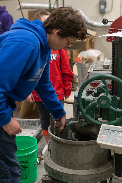 Concrete canoe co-captain Zane Beattie scrapes the sides of the concrete mixer to ensure that everything gets properly mixed together. (Alex Todd | Collegian Media Group)