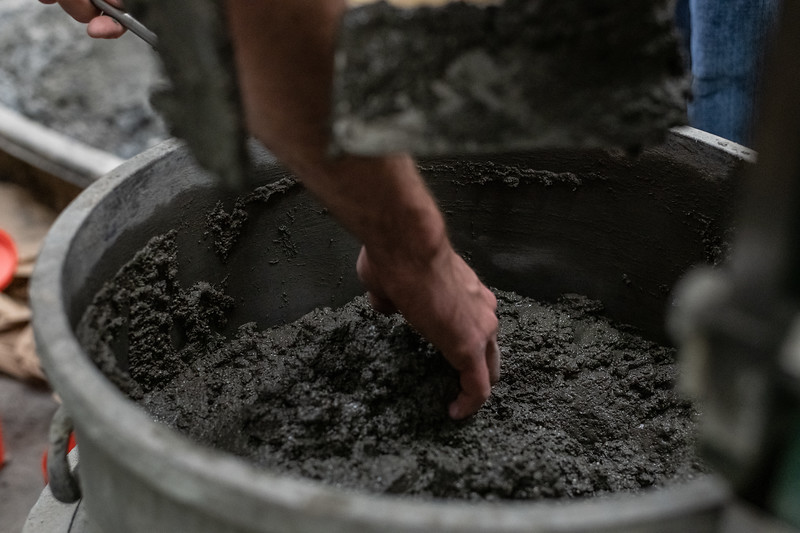 Junior in Civil Engineering Ian Mosier gets a scoop of freshly mixed concrete to check the texture during a concrete canoe team meeting on November 1, 2018. (Alex Todd | Collegian Media Group)