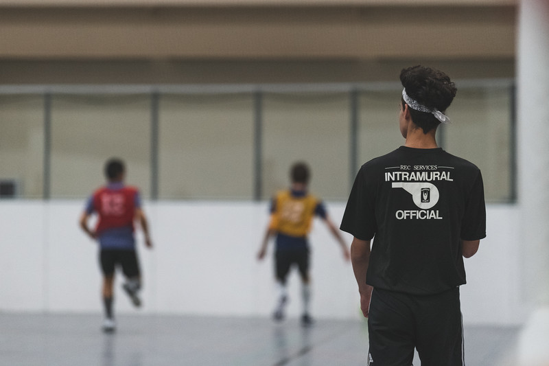 An intramural referee watches two players try to gain control of the ball during an indoor soccer match at the rec on November 7, 2018. (Alex Todd | Collegian Media Group)