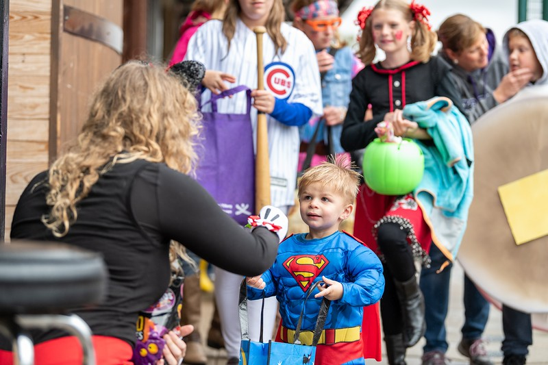 Superman collects candy from Minnie Mouse outside of O'Malley's as part of the annual Trick or Treat event in Aggieville on October 12, 2018. (Alex Todd | Collegian Media Group)