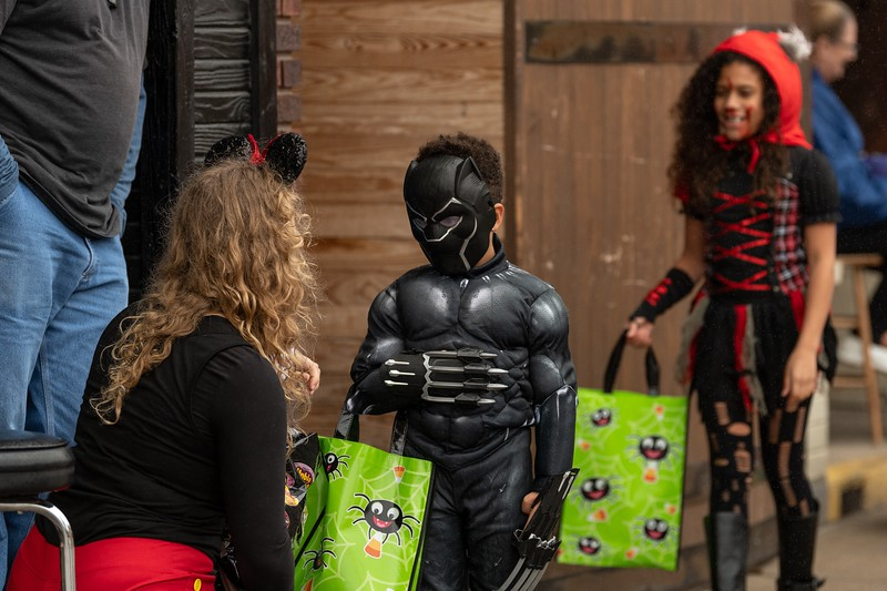 The Black Panther collects some Halloween candy from Minnie Mouse outside of O'Malley's during the annual Trick or Treat event in Aggieville on October 12, 2018. (Alex Todd | Collegian Media Group)