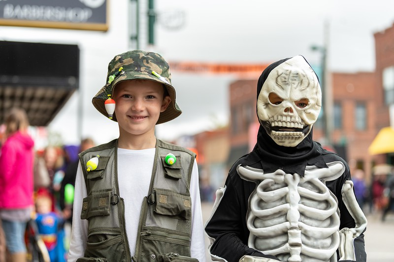 A fisherman and a spooky skeleton pose for a picture during the annual Trick or Treat event in Aggieville on October 12, 2018. (Alex Todd | Collegian Media Group)