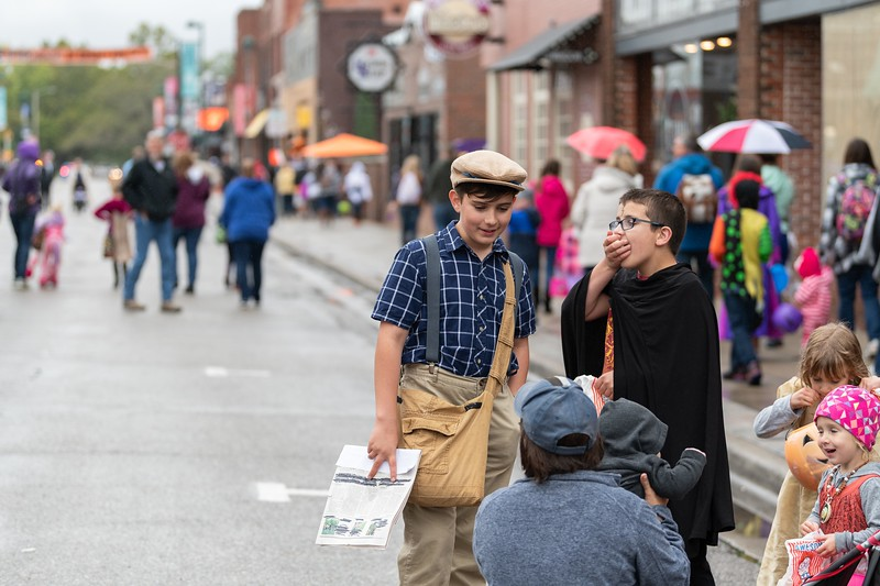 A paper boy and his friends enjoy some candy  during the annual Trick or Treat event in Aggieville on October 12, 2018. (Alex Todd | Collegian Media Group)