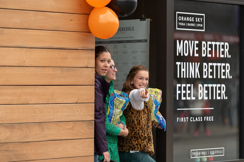 Employees of Orange Sky Yoga pose for a photo as they hand out Halloween candy to kids during the annual Trick or Treat event in Aggieville on October 12, 2018. (Alex Todd | Collegian Media Group)