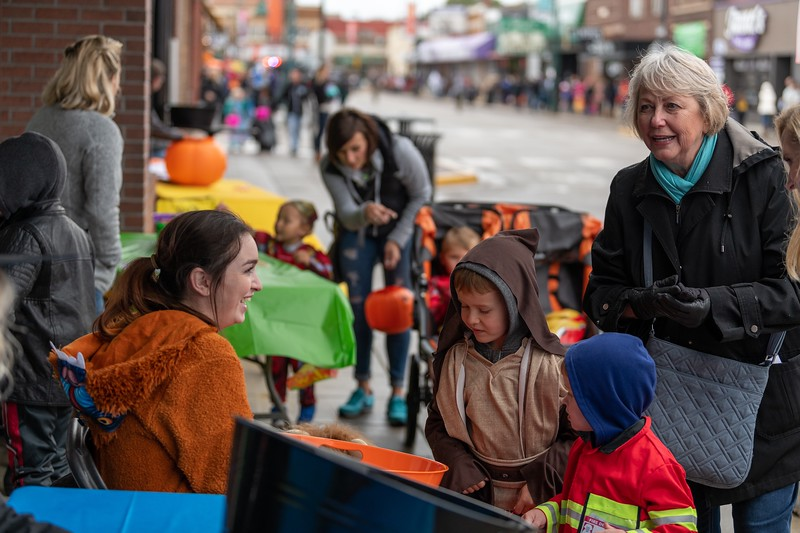 A young jedi and a firefighter collect some Halloween candy at the annual Trick or Treat event in Aggieville on October 12, 2018. (Alex Todd | Collegian Media Group)