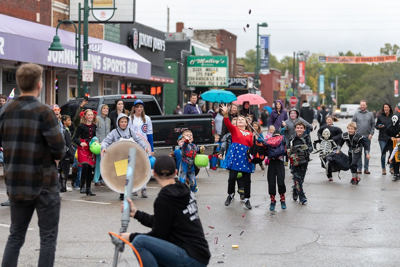 As it rains candy, kids hurry over to collect it after it's shot out of a candy cannon during the annual Trick or Treat event in Aggieville on October 12, 2018. (Alex Todd | Collegian Media Group)