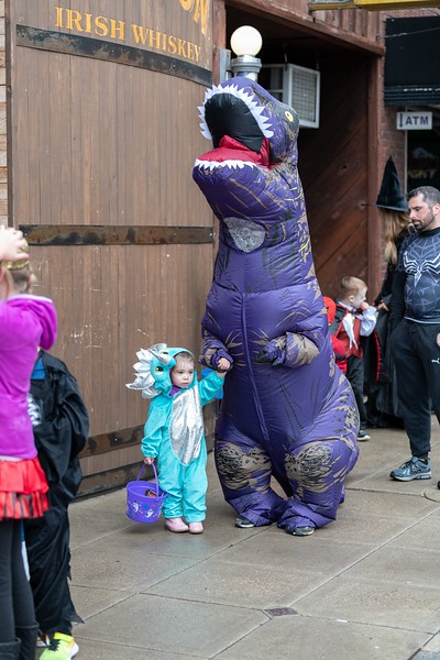 A purple T-Rex and it's young dinosaur wait in line for the annual Trick or Treat event in Aggieville on October 12, 2018. (Alex Todd | Collegian Media Group)