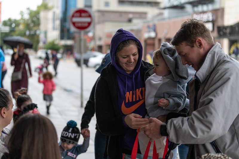 A family collects halloween candy with their child outside of Rallyhouse in Aggieville on October 12, 2018. (Alex Todd | Collegian Media Group)