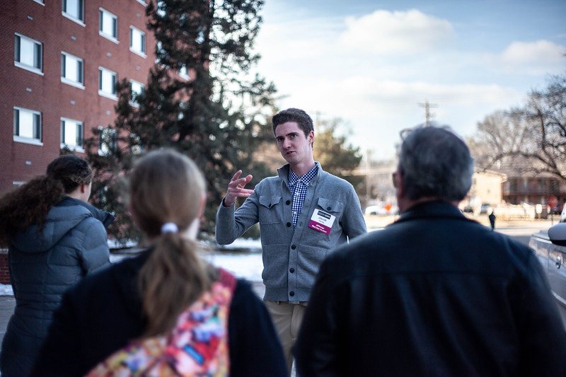 Jacob Bandy, senior transfer student in Environmental Design, walks backwards as he talks about the dorm policy at K-State to perspective students. Bandy is assiting on this tour as a part of his training to be a campus tour guide.<br /> (Alanud Alanazi   Collegian Media Group)