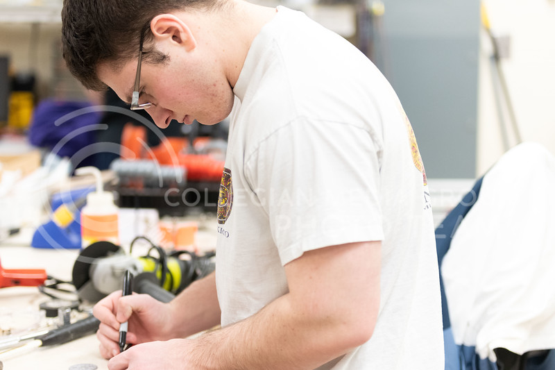 K-State, Jr majoring in Mechanical Engineering, Kyle Bannon, member of the K-State Combat Robotics team, measures and marks the shaft before they begin to cut. (Dylan Connell | Collegian Media Group)