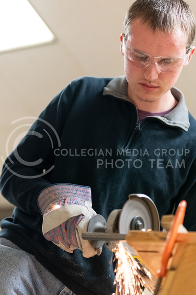 K-State, Sr majoring in Electrical Engineering, Eero Halbleib, member of the K-State Combat Robotics team, cuts spare shaft parts used to hold the weapons on their Bot. (Dylan Connell | Collegian Media Group)