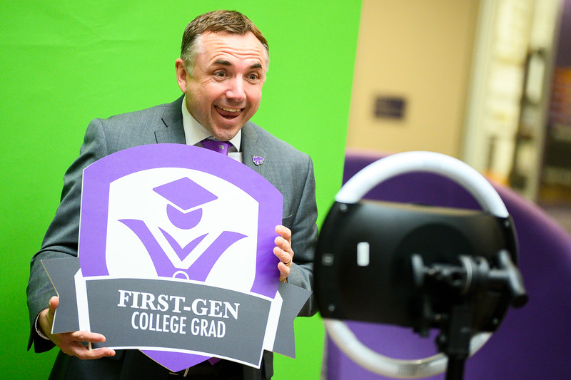 """Dr. Thomas Lane, Kansas State University vice president for student life and dean of students, holds a sign saying """"FIRST-GEN COLLEGE GRAD"""" while posing in a photo booth. National First-generation College Student Celebration day is Friday, Nov. 8. The Union Program provided food, drinks, music, and games for all interested in celebrating the success of first-generation college students, faculty, and staff on K-State's campus. (Dylan Connell 