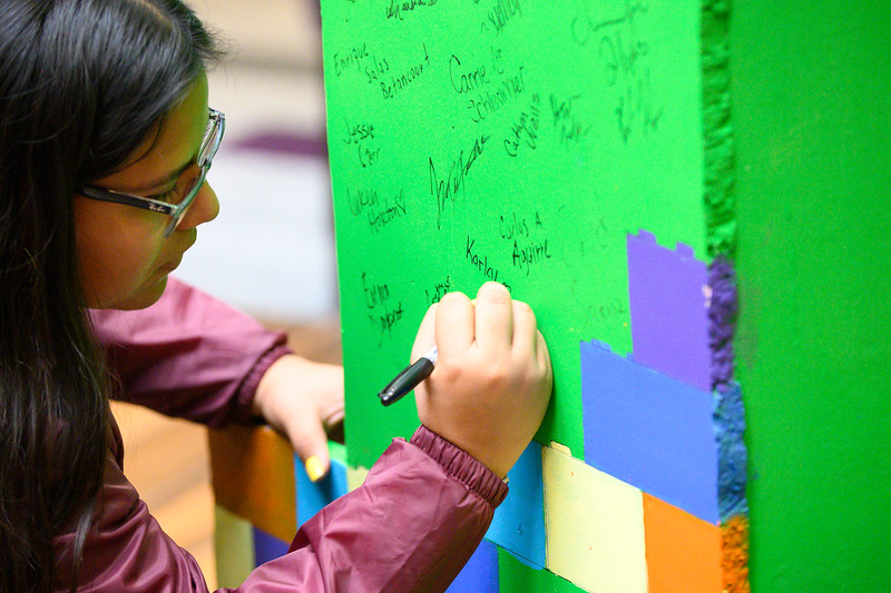 Karla Lopez, Sophomore studying Industrial Engineering at K-State, writes her name on the giant foam number one. Representing and supporting first generation students. National First-generation College Student Celebration day is Friday, Nov. 8. The Union Program provided food, drinks, music, and games for all interested in celebrating the success of first-generation college students, faculty, and staff on K-State's campus. (Dylan Connell | Collegian Media Group)
