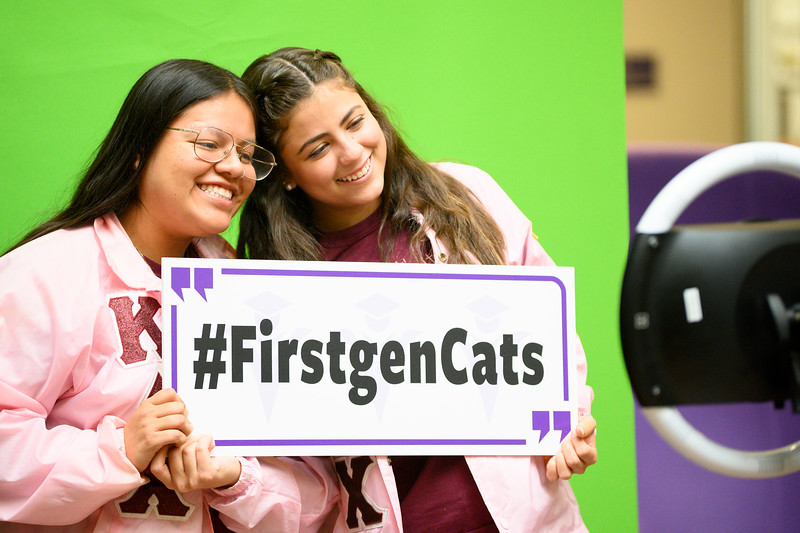 """Tatiana Briceño, sophomore studying mathematics and Spanish at K-State and  Leslie Ramirez, senior at K-State studying Education-English and Spanish Translation hold a sign saying """"#FirstgenCats"""" while standing in front of a photo booth. National First-generation College Student Celebration day is Friday, Nov. 8. The Union Program provided food, drinks, music, and games for all interested in celebrating the success of first-generation college students, faculty, and staff on K-State's campus. (Dylan Connell 