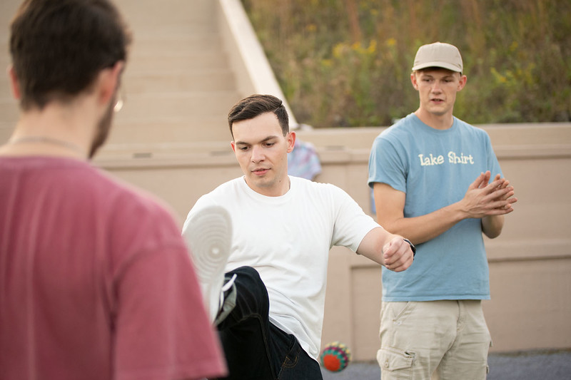Andrew Stene kicks the hacky sack while Seth Montgomery and Hunter Spicer watch. Oct 3, 2019. (Dylan Connell | Collegian Media Group)