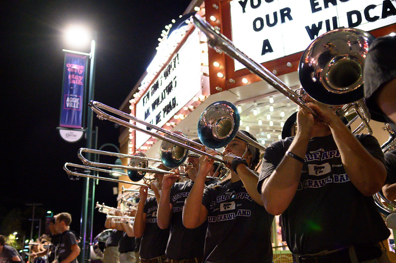 Trombone players join the rest of the marching band in their last performance of the night during the Pub Crawl. Wildcat Victory was one of the songs played from the band's repertoire as they took over Aggieville the night before K-State defeated TCU 24-17 on Oct 18, 2019. (Dylan Connell | Collegian Media Group)