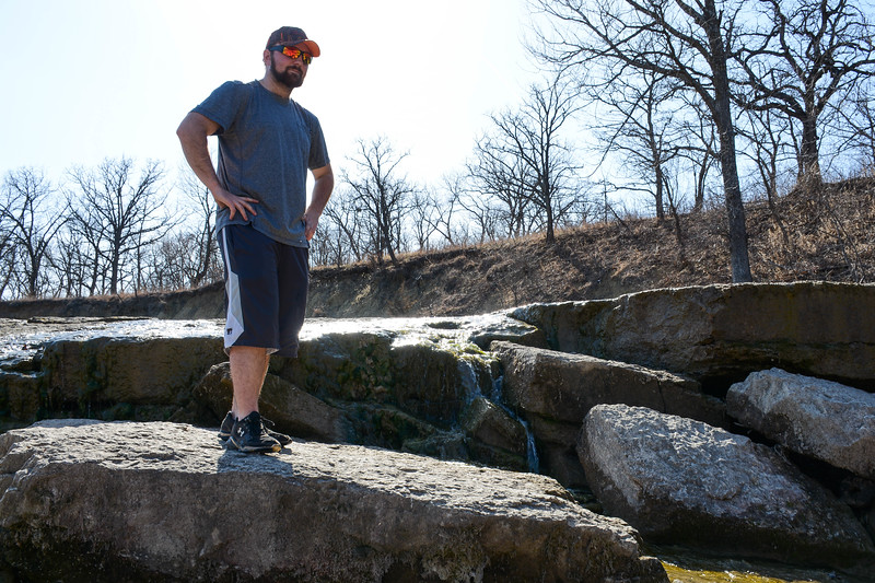 Ryan Lierz, Senior in grain science climbs along the rock surfaces lining a the falls at Pillsbury Crossing Wildlife Area. The falls are just a few dozen feet down river from the crossing and can be reached from parking spots next to the east side of Pillsbury Crossing. (Conrad Kabus | Collegian Media Group)