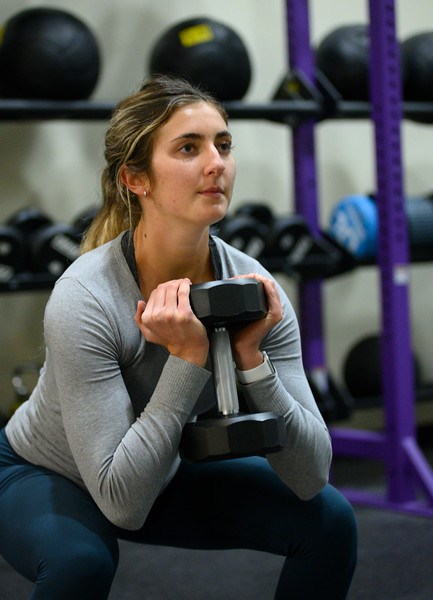 KSU student ,Josie Lewin, senior studying Elementary Education squats dumbbells while working out at the K-State, Chester E. Peters Recreation Complex. Oct 23, 2019. (Dylan Connell | Collegian Media Group)