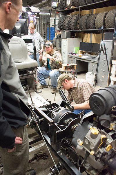 Members of the Helwig Farms K-State Quarter-Scale Tractor Team work on the prototype drive train of the tractor they are building in the basement of Seaton Hall on Thursday, March 8, 2018. Their tractor will compete during the second weekend in June in Peoria, Illinois. (Tiffany Roney   Collegian Media Group)
