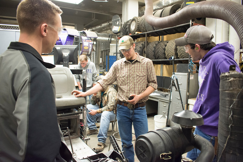 Ryan Zecha (far left), industry advisor for the Helwig Farms K-State Quarter-Scale Tractor Team, discusses the tractor's prototype drive train with E.J. Swihart (center), senior in biological systems engineering, and Curtis Doughramaji, senior in biological systems engineering. Also pictured: Evan Ridder, sophomore in biological systems engineering, and Jace Shirley, sophomore in agriculture technology management (partly hidden). Their tractor will compete during the second weekend in June in Peoria, Illinois. (Tiffany Roney   Collegian Media Group)