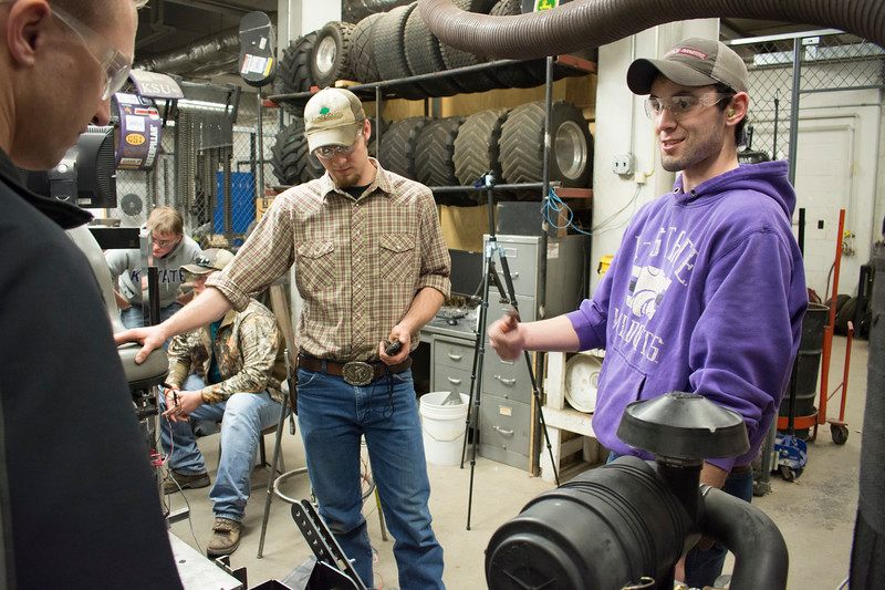 Curtis Doughramaji, senior in biological systems engineering, talks with Ryan Zecha (far left), industry advisor for the Helwig Farms K-State Quarter-Scale Tractor Team, and E.J. Swihart (center), senior in biological systems engineering, about the prototype drive train of the tractor they are building in the basement of Seaton Hall on Thursday, March 8, 2018. (Tiffany Roney   Collegian Media Group)