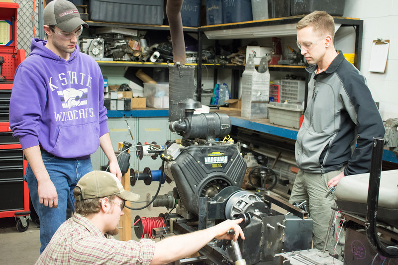 Curtis Doughramaji (from left), senior in biological systems engineering; E.J. Swihart, senior in biological systems engineering; and Ryan Zecha, industry advisor for the Helwig Farms K-State Quarter-Scale Tractor Team, work on the prototype drive train of the tractor they are building in the basement of Seaton Hall on Thursday, March 8, 2018. Their tractor will compete during the second weekend in June in Peoria, Illinois. (Tiffany Roney   Collegian Media Group)