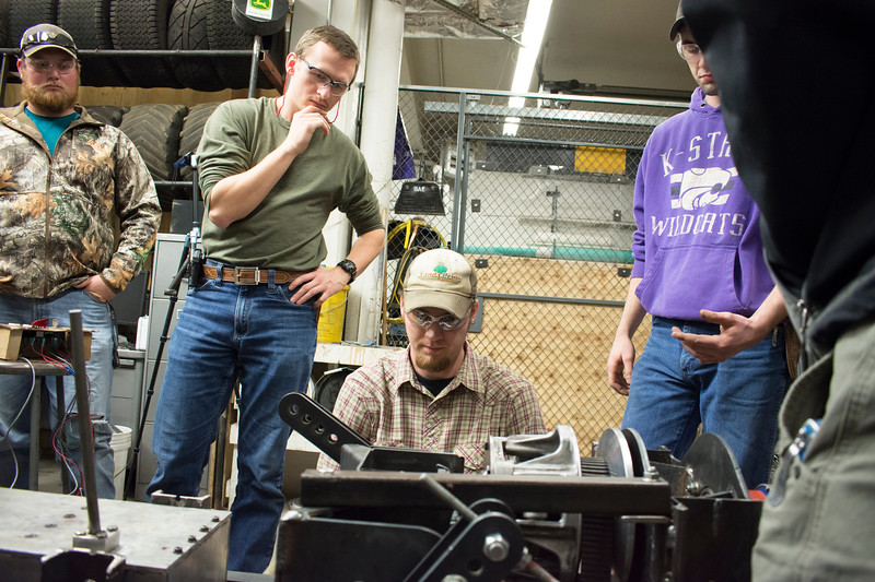 Jace Shirley (from left), sophomore in agricultural technology management; Alex Nytko, senior in biological systems engineering; E.J. Swihart, senior in biological systems engineering; and Curtis Doughramaji, senior in biological systems engineering, who are members of the Helwig Farms K-State Quarter-Scale Tractor Team, test the prototype drive train of the tractor they are building in the basement of Seaton Hall on Thursday, March 8, 2018. The contest will be held the second weekend in June in Peoria, Illinois. (Tiffany Roney   Collegian Media Group)