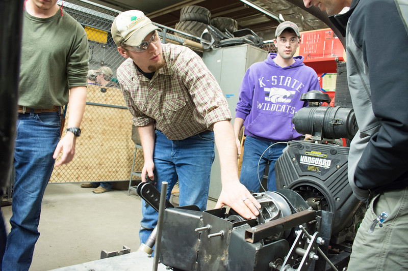 E.J. Swihart (center), senior in biological systems engineering, talks with Ryan Zecha (far left), industry advisor for the Helwig Farms K-State Quarter-Scale Tractor Team, as they work with Alex Nytko (far left), senior in biological systems engineering, and Curtis Doughramaji, senior in biological systems engineering, to test the prototype drive train of the tractor they are building in the basement of Seaton Hall on Thursday, March 8, 2018. The contest will be held the second weekend in June in Peoria, Illinois. (Tiffany Roney   Collegian Media Group)