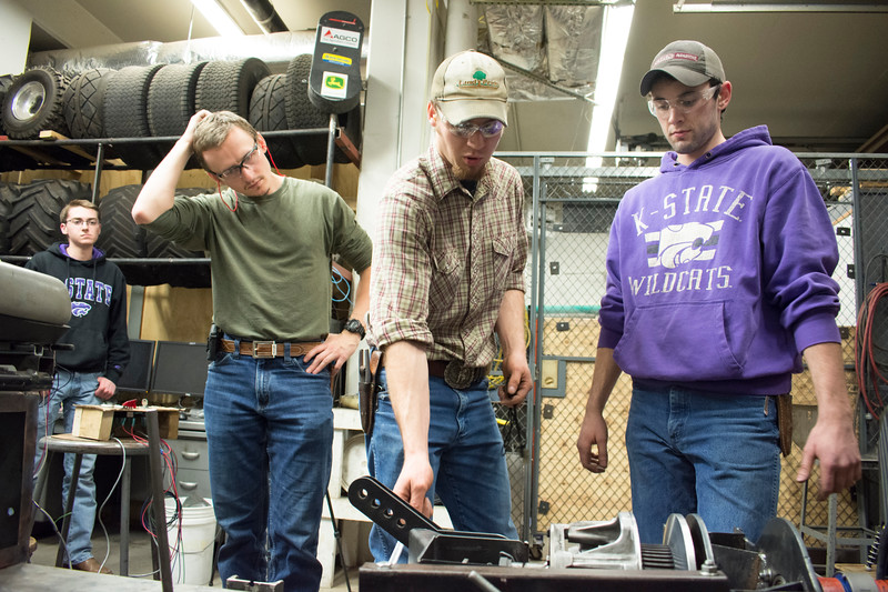 Corbin Baldwin (from left), freshman in biological systems engineering, listens as Alex Nytko, senior in biological systems engineering; E.J. Swihart, senior in biological systems engineering; and Curtis Doughramaji, senior in biological systems engineering, test the prototype drive train of the tractor they are building in the basement of Seaton Hall on Thursday, March 8, 2018. The students are members of the Helwig Farms K-State Quarter-Scale Tractor Team. Their tractor will compete during the second weekend in June in Peoria, Illinois. (Tiffany Roney   Collegian Media Group)