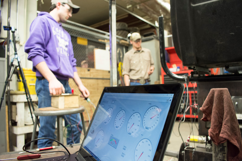 Curtis Doughramaji (left), senior in biological systems engineering, and E.J. Swihart, senior in biological systems engineering, Helwig Farms K-State Quarter-Scale Tractor Team, test the prototype drive train of the tractor they are building in the basement of Seaton Hall on Thursday, March 8, 2018. Also shown: the computer screen displays the tractor's performance in terms of torque, RPM, force and other measurements. (Tiffany Roney   Collegian Media Group)