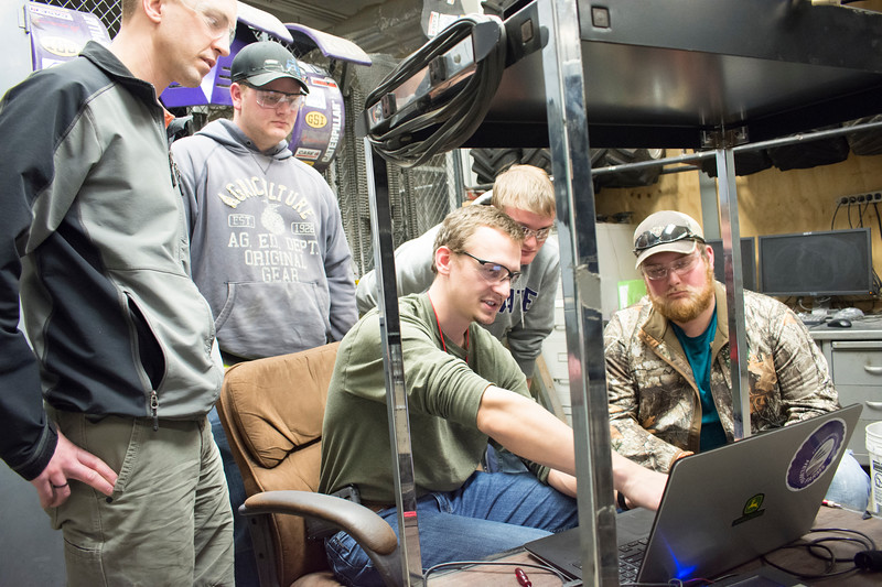 Alex Nytko, senior in biological systems engineering, discusses a computer display — which shows performance in terms of torque, RPM, force and other measurements — with fellow members of the Helwig Farms K-State Quarter-Scale Tractor Team and with Ryan Zecha (far left), industry advisor for the team. Team members pictured in the back row: Grant Friesen (from left), sophomore in biological systems engineering; Evan Ridder, sophomore in biological systems engineering; and Jace Shirley, sophomore in agricultural technology management. The group met in the basement of Seaton Hall on Thursday, March 8, 2018. (Tiffany Roney   Collegian Media Group)