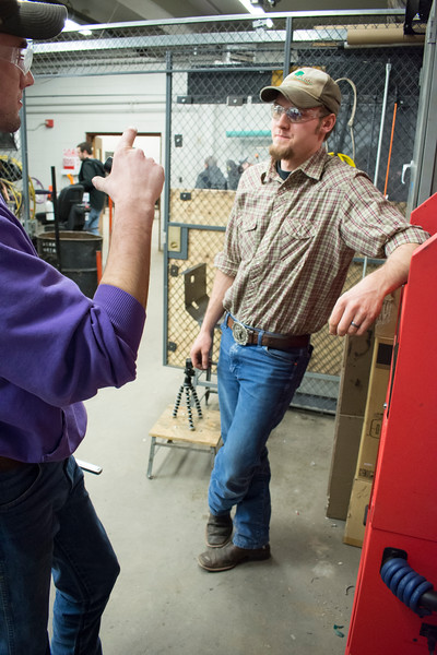 Curtis Doughramaji (left), senior in biological systems engineering, talks with E.J. Swihart (center), senior in biological systems engineering, about the prototype drive train of the tractor they are building in the basement of Seaton Hall on Thursday, March 8, 2018. Their tractor will compete during the second weekend in June in Peoria, Illinois. (Tiffany Roney   Collegian Media Group)