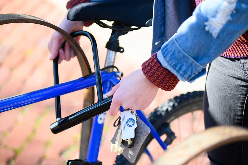 Sydney Burton, K-State Sophomore majoring in Kinesiology, Pre-Physical Therapy. Sydney uses her bike to transport around campus. She is photographed unlocking her bike on a brisk morning in December. (Dylan Connell | Collegian Media Group)