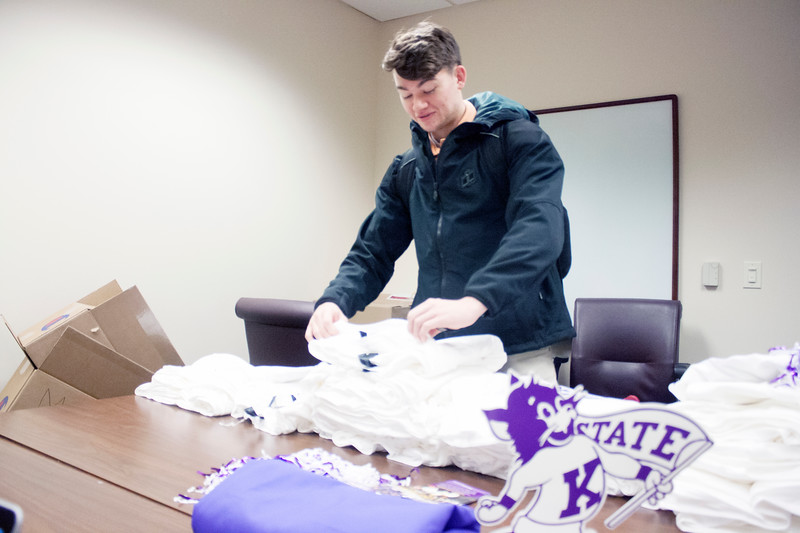 Zachary Langston, sophomore in human development and family science, selects a Wildcats Forever T-shirt on Tuesday, March 27, 2018 at the K-State Alumni Center. (Tiffany Roney | Collegian Media Group)