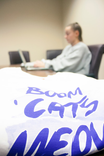 """Boom 'Cats Meow"" is printed on the front of T-shirts awaiting pickup at the Wildcats Forever T-shirt event on Tuesday, March 27, 2018 at the K-State Alumni Center. In the background, Megan Clapp, senior in chemical engineering, volunteers at event. (Tiffany Roney 