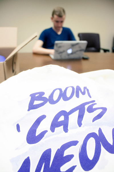 """Boom 'Cats Meow"" is printed on the front of T-shirts awaiting pickup at the Wildcats Forever T-shirt event on Tuesday, March 27, 2018 at the K-State Alumni Center. In the background, Colby Works, sophomore in kinesiology, volunteers at event. (Tiffany Roney 