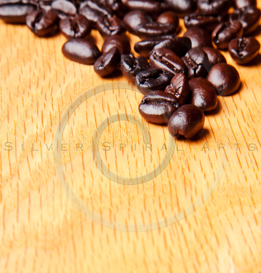 whole brown coffee beans on wood