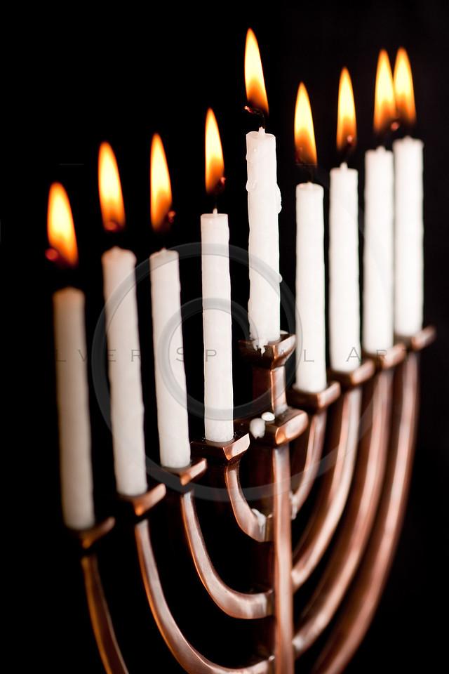 Beautiful lit hanukkah menorah on black background.