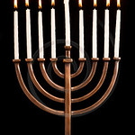 Beautiful lit hanukkah menorah on black velvet.