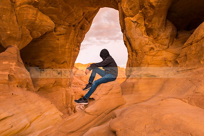 Boy sitting under the desert arch at Timna Park, Eilat Mountains