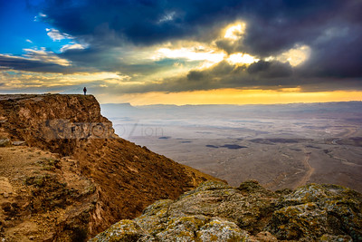 Man on a desert cliff with cloudy sunset, Negev Desert