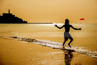 Man playing frisbee on Tel Aviv beach, with Jaffa in the background