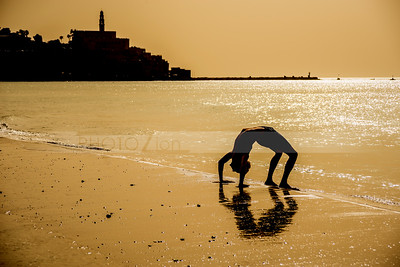 Man doing yoga on Tel Aviv beach, with Jaffa in the background