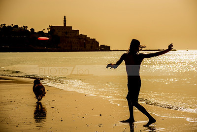 Man playing frisbee with his dog on Tel Aviv beach, with Jaffa in the background
