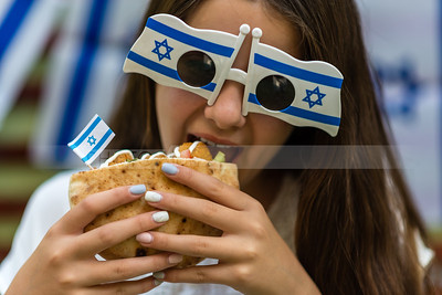 Israel's Independence Day; Israeli girl eating pita with falafel