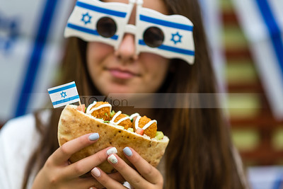 Israeli girl holding pita with falafel; Independence Day